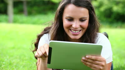smiling-woman-touching-a-tablet-computer-in-a-park